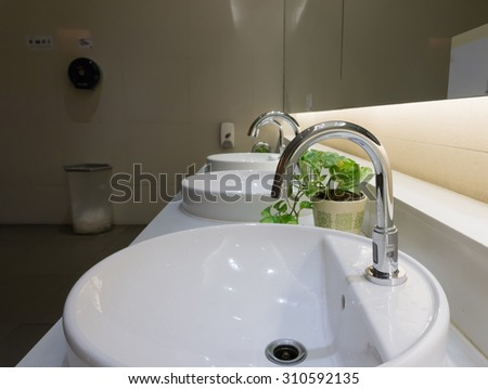 washbasins and faucet on granite counter in restroom - stock photo