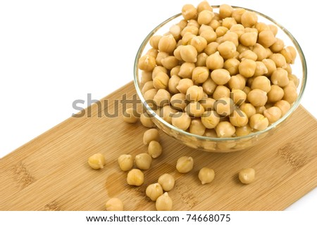 Washed and drained canned chickpeas in glass dish on bamboo board isolated on white background - stock photo
