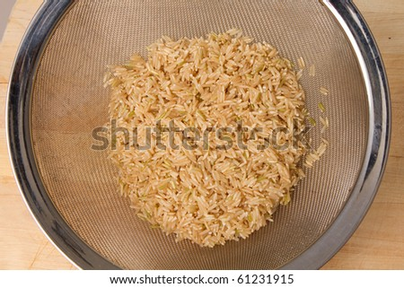 Washed and strained brown rice - stock photo