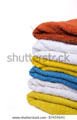 washed nicely color coordinated towels white background - stock photo