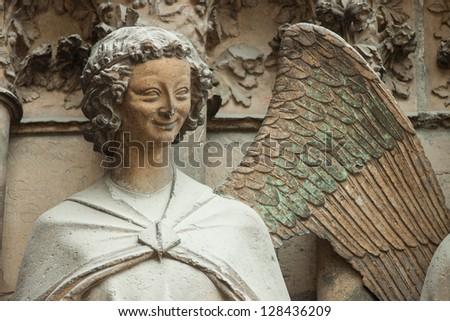 Washed-out statue of angel on the front of  Cathedral of Notre-Dame, Reims, France - stock photo