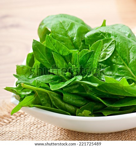 Washed spinach leaves in a bowl on a wooden table - stock photo