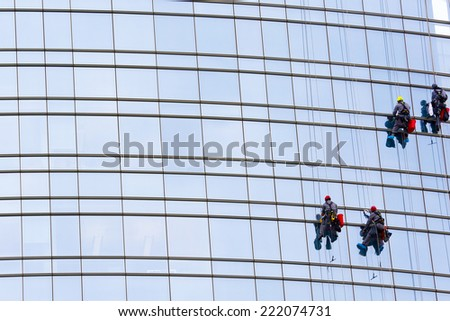 washers clean the facade of the skyscraper window clinging to the ropes