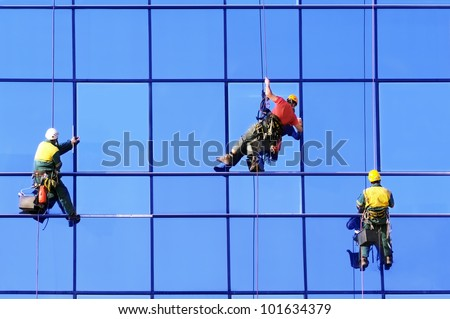 Washers wash the windows of modern skyscraper - stock photo