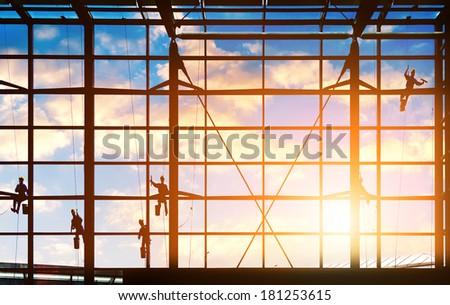 Washers wash the windows of modern skyscraper - stock photo