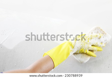 washing a soapy white car with a yellow sponge.  - stock photo