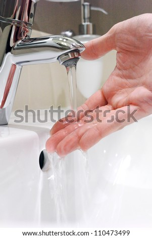 Washing arm  in sink bathroom. - stock photo
