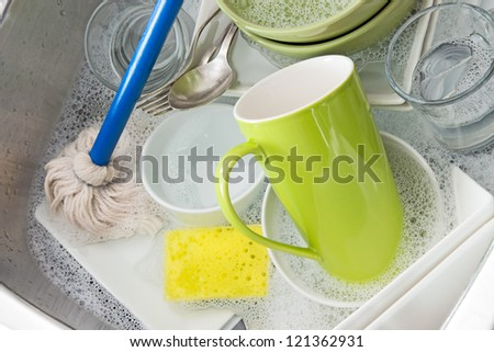 Washing bright dishes in the kitchen sink. - stock photo