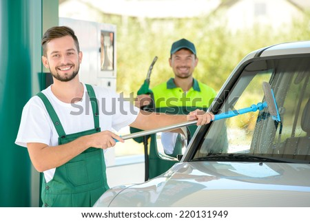 Washing car window while filling petrol cars at gas station - stock photo