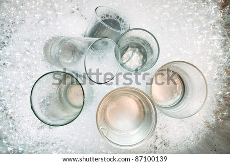 Washing dirty glasses with detergent and water - stock photo