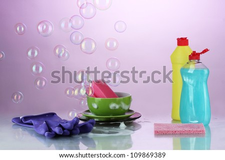 Washing dishes. Cleaning products on bright violet background - stock photo