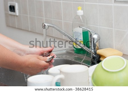 Washing dishes in the kitchen - stock photo