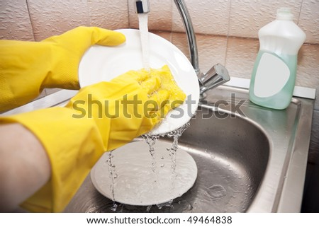 washing dishes under running water with a focus on the plate - stock photo
