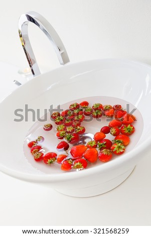 Washing fresh Strawberries in the Sink - stock photo