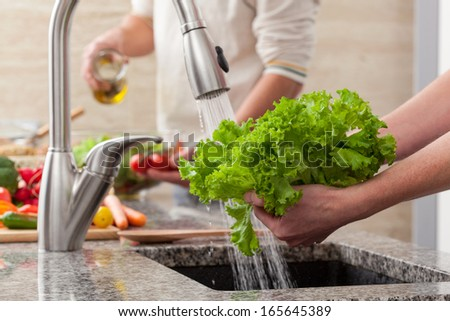 Washing fresh vegetables for a salad with an alive oil - stock photo