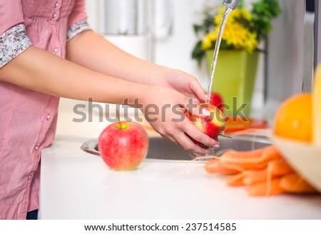 Washing fruit, woman washing red apple under the tap - stock photo