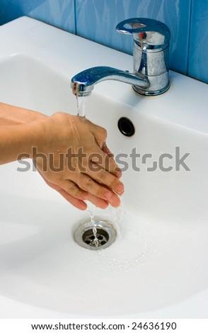 Washing hands in bathroom - stock photo