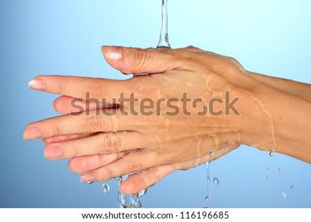 Washing hands on blue background close-up - stock photo