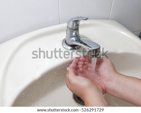 Washing hands under flowing tap water