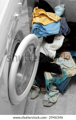 Washing machine and lot of dirty clothes. - stock photo