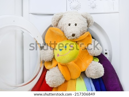 Washing machine, children's toy and colorful laundry to wash - stock photo