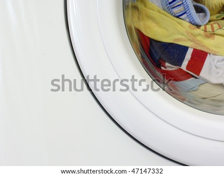 Washing machine fragment with the clothes loaded - stock photo