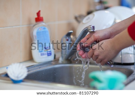 Washing of the dishes - woman hands rinsing dishes under running water in the sink (color toned image; shallow DOF) - stock photo