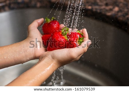 washing strawberries under a faucet - stock photo