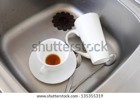 Washing up. White coffee cups in the kitchen sink. - stock photo