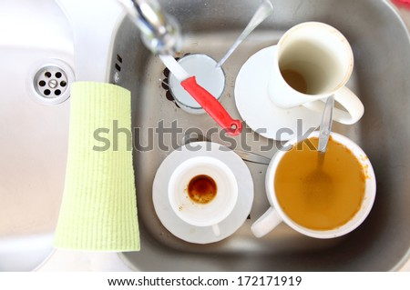 Washing up. White dirty dishes in the kitchen sink. - stock photo