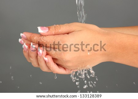 Washing woman's hands on gray background close-up