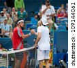 WASHINGTON - AUG 1: Tommy Haas (GER) and Leonardo Mayer (ARG) shake hands after Haas' win at the Citi Open tennis tournament on August 1, 2012 in Washington. - stock photo