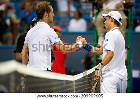 WASHINGTON - AUGUST 1: Kei Nishikori (JPN) and Richard Gasquet  (FRA) shake hands after Gasquet won at the Citi Open tennis tournament on August 1, 2014 in Washington DC - stock photo