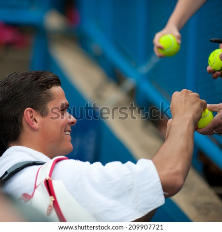 WASHINGTON - AUGUST 1: Milos Raonic (CAN) gives autographs after defeating Steve Johnson (USA, not pictured) at the Citi Open tennis tournament on August 1, 2014 in Washington DC - stock photo