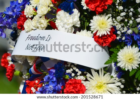 "WASHINGTON, D.C. - MAY 27, 2013:A wreath with ""Freedom is not Free"" phrase during Memorial Day at the Vietnam Veterans Memorial on May 26, 2014, in Washington, D.C."