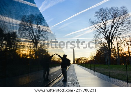 Washington DC - A Veteran looks for a name at Vietnam Veterans Memorial Wall  at sunrise - stock photo