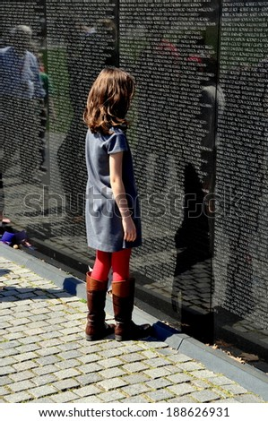 Washington, DC - April 10, 2014:  A little girl studies names inscribed on the black granite wall of the Vietnam War Memorial on the National Mall - stock photo