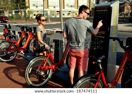 Washington, DC - April 13, 2104:  Young couple renting bicycles at a Washington Capitol Bike Share docking station on North Carolina Avenue S.E. - stock photo