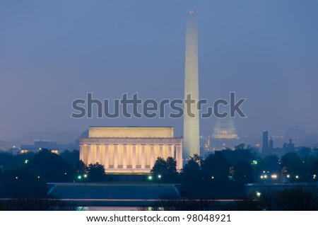Washington DC city view during an early foggy sunrise, including Lincoln Memorial, Monument and Capitol building - stock photo