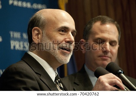 WASHINGTON, DC - FEBRUARY 3: U.S. Federal Reserve Board Chairman Ben Bernanke speaks at the National Press Club as Club President Mark Hamrick looks on, February 3, 2011 in Washington, DC - stock photo