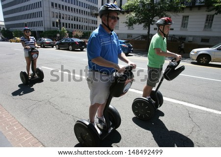 WASHINGTON, DC - JULY 29: Tourists operate Segways during a Segway tour along the National Mall on July 29, 2013 in Washington.  - stock photo