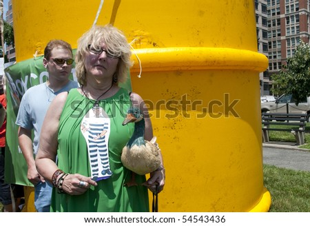 WASHINGTON, DC - June 4: Female demonstrator holds stuffed duck in front of giant inflatable oil barrel in protest against BP oil spill, June 4, 2010 in Washington, DC - stock photo