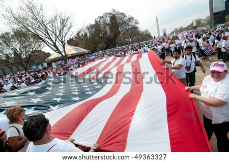 WASHINGTON, DC - MARCH 21: A giant American flag is carried among some 200,000 immigrants' rights activists flood the National Mall on March 21, 2010 in Washington DC. - stock photo