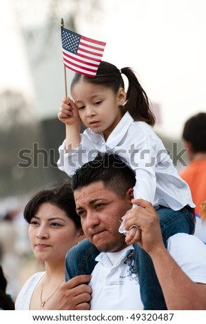 WASHINGTON, DC - MARCH 21: A girl and her father stand with some 200,000 immigrants' rights activists flood the National Mall to demand comprehensive immigration reform on March 21, 2010 in Washington DC. - stock photo