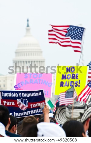 WASHINGTON, DC - MARCH 21: The U.S. Capitol building in the distance, some 200,000 immigrants' rights activists flood the National Mall to demand comprehensive immigration reform on March 21, 2010 in Washington DC. - stock photo