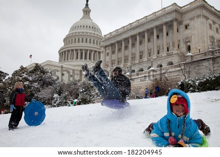 WASHINGTON, DC - MARCH 17: Unexpected snow day on March 17, 2014 in Washington, DC. Schools were closed, children and adults are sledding on the US Capitol lawn. - stock photo