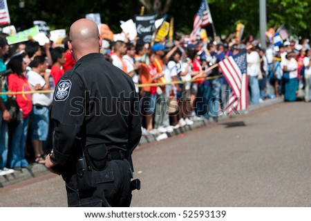 WASHINGTON, DC - MAY 1: A policeman confronts crowds of immigration reform activists during a protest on May 1, 2010 at the White House in Washington, DC. - stock photo