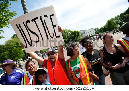 "WASHINGTON, DC - MAY 1: An immigration reform activist holds a sign reading ""Justice"" during a protest at the White House on May 1, 2010 in Washington, DC. - stock photo"