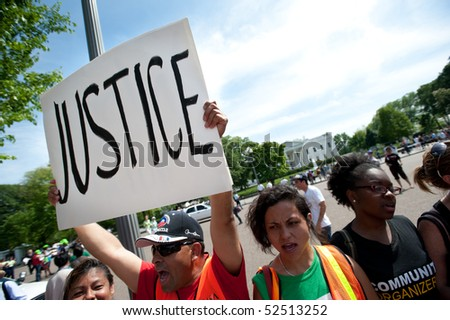 "WASHINGTON, DC - MAY 1: An immigration reform activist holds a sign reading ""Justice"" during a protest on May 1, 2010 at the White House in Washington, DC. - stock photo"
