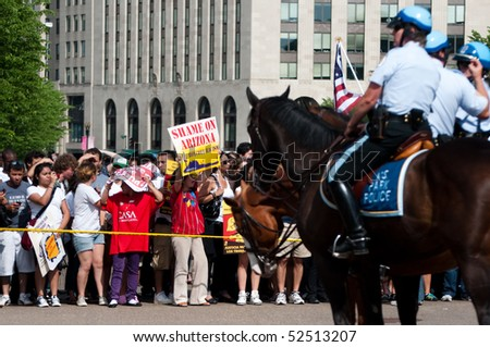 WASHINGTON, DC - MAY 1: Police on horseback watch as immigration reform activists protest on May 1, 2010 at the White House in Washington, DC. - stock photo